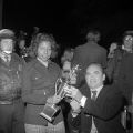 Terry Points receiving her homecoming queen trophy from Governor George Wallace, possibly at the pep rally the night before the homecoming game at the University of Alabama.