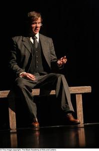 Actor dressed in suit speaking Ellis Island