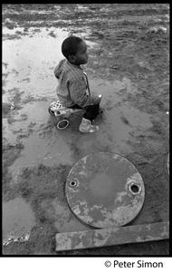 Young boy riding a toy car in the mud, Resurrection City