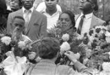 Close-up of mourners standing behind floral arrangements at Martin Luther King, Jr.'s grave site in South View Cemetery.