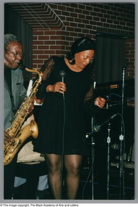 Photograph of Benita Arterberry holding a microphone next to a man playing a saxophone Al Lipscomb Tribute