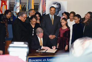 US President William Jefferson Clinton (center) is surrounded by the family members of US Army First Lieutenant (1LT), Henry O. Flipper, the first African American to graduate from the US Military Academy at West Point, as the President signs a document pardoning 1LT Flipper for a 1882 Army conviction for conduct unbecoming an officer and a gentleman. The dishonorable discharge accompanying the conviction had been changed to honorable in 1976