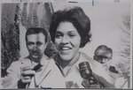 [Charlayne Hunter smiling as she speaks into microphones to reporters]