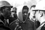Simuel Schutz, Jr., speaking to policemen who have lined up across a road to block their demonstration in Tuskegee, Alabama, to protest the murder of Samuel L. Younge, a civil rights worker.