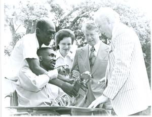 Photograph of Dr. Robert L. Bennett explaining the operation of a patient's hand splint to Georgia governor Jimmy Carter and Rosalynn Carter at the Georgia Warm Springs Foundation, Warm Springs, Meriwether County, Georgia, 1971-1975?