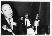 Mississippi State Sovereignty Commission photograph of Martin Luther King, Jr. speaking at a conference for the Southern Christian Leadership Conference with Anne Braden, Carl Braden and James A. Dombrowski seated in the background, Birmingham, Alabama, 1962 September 27