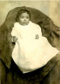 Unidentified baby in gown on chair