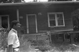 Norman Lumpkin,news director for WRMA radio, walking in the overgrown yard of a small clapboard house.
