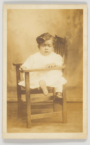 Thumbnail for Photographic postcard of an infant in a wooden chair