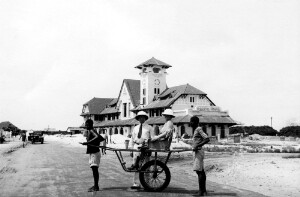 Jackson Davis (standing) and Corinne Davis (seated in a human held buggy) in a street in Africa.