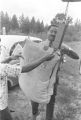 Norman Lumpkin, news director for WRMA radio, and a woman hanging a bag of cotton on a scale.