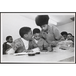A boy talks to an art instructor while working on his project at the Boys' Clubs of Boston