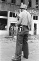 Police officer standing guard in the street across from the Silver Sands Restaurant and the Liberty Contracting Company, which were damaged during the 16th Street Baptist Church bombing.