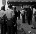 Police officers and bystanders in front of Social Cleaners across from 16th Street Baptist Church, after the church was bombed.