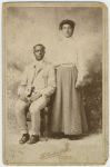 Studio portrait of a young couple, he seated, she with hand on his shoulder