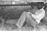 Man sitting in the shade under a trailer full of cotton, which is parked at the field of Mrs. Minnie B. Guice near Mount Meigs in Montgomery County, Alabama.