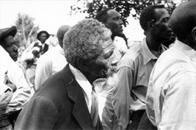 Group of African American men listen to a speaker during an outdoor STFU meeting