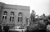 Young African American man speaking through the PA system of a fire department truck after the bombing of 16th Street Baptist Church in Birmingham, Alabama.