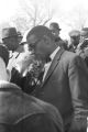 Dr. Burcham Phillips speaking into a microphone during a student demonstration in Tuskegee, Alabama, to protest the murder of Samuel L. Younge, a civil rights worker.