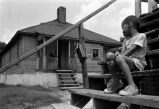 Negro boy sitting on steps outside big house.