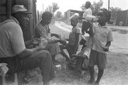 Man, woman, and children, eating and drinking outside a barn or shed near Mount Meigs in Montgomery County, Alabama.