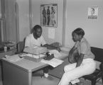 Students discussing paperwork with a professor or counselor at Tuskegee Institute in Tuskegee, Alabama.