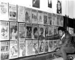 Man in front of wall of posters