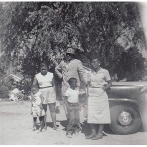 A family poses in a dirt driveway.