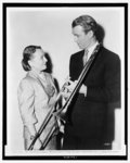 """Mrs. Glenn Miller, left, widow of the famous bandleader, presented James Stewart, right, who plays her husband in the title role in """"The Glenn Miller Story,"""" with the trombone which her husband actually played prior to his untimely death during World War II"""