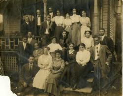Group posed on front porch steps of Alpha Phi Alpha House, 1017 Catherine St. Ann Arbor