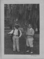 Photograph. Unidentified man on golf course with African-American caddy.
