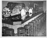 Two male bartenders wearing short white serving coats stand behind bar at Slim Jenkins Restaurant and Bar Oakland, California