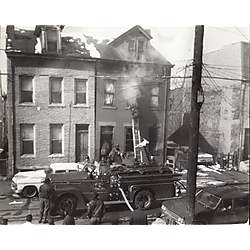 Fire fighters battling a fire in a three story brick row house