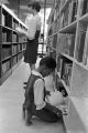 Little girl looking at a book from a shelf at the Montgomery Public Library.