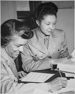 """WAACs at work in Temp. Bldg. `M', 26th Street, Washington, DC, WAAC Headquarters. Left to right: Lts. Harriet West and Irma Cayton,...going over their recruiting schedule report."""