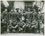 Group portrait of members of the Camp Lee boxing team, mostly African American, posing with Commanding General of the Post, Brigadier General R. C. L. Graham (holding trophy), Camp Lee, Virginia