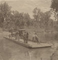 African American man operating a ferry as it carries two horse-drawn carriages and their passengers across the Cahaba River.
