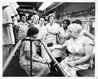 Garment workers at the Abe Schrader Shop listen to funeral services for Dr. Martin Luther King, Jr., on a portable radio, April 9, 1968