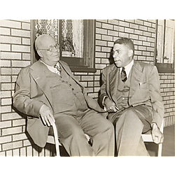 Two men sitting before brick wall with windows and lace curtains