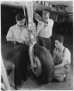 At an eastern aircraft factory, Philip Leung, Chinese, Marcell Webb, Negro, and an unidentified White worker adjust the retractable landing gear of a pursuit plane on the final assembly line.