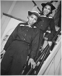 """Two Negro SPARS pause on the ladder of the dry-land ship `U.S.S. Neversail' during their `boot' training at the U.S. Coast Guard Training Station, Manhattan Beach, Brooklyn, NY. They are recent enlistees and have the ratings of apprentice seamen. In front is SPAR Olivia Hooker and behind her is SPAR Aileen Anita Cooks."""