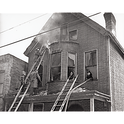 Fire fighters with ladders and hoses on second and third floors of brick house
