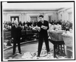 """[In a scene from the movie, """"Mr. Smith Goes to Washington"""", Jimmy Stewart examines numerous lettes from baskets as well as those littered on the floor of the Senate, as Claude Raines (left) and others look on]"""
