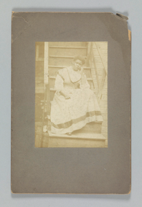 Albumen print of an unidentified woman sitting on stairs