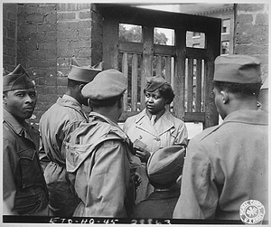 """The first Negro WACs to arrive [on] the continent of Europe were 800 girls of the 6888th Central Postal Directory Bn, who had also been the first to arrive in England. After the battalion had set up its facilities at Rouen, France, it held an `open house', which was attended by hundreds of Negro soldiers. Pvt. Ruth L. James,...of the battalion area is on duty at the gate."""