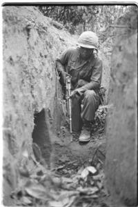Negro soldier of the 1st Infantry Division searching a Vietcong trench.