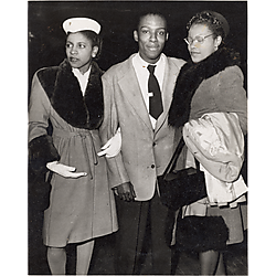 A young man and two women in fur-trimmed coats