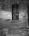 Woman standing in the window of a house that was either damaged by the bombing of Allen Temple AME Church, or in a separate incident around the same time.