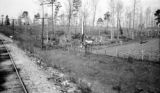 United States, farmer plowing fields across from railroad tracks