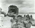 African American sailors rolling out barrels from a vessel to shore of Biak Islands